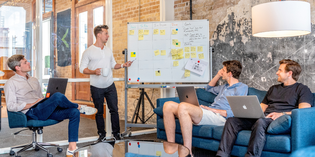 four-people-at-a-whiteboard-meeting